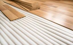Tejas del piso laminado con el efecto de madera que pone en la espuma baja blanca, listas para ser instalado en la tierra, mejora fotografía de archivo libre de regalías