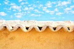 Tejas onduladas sobre una pared del adobe con el cielo azul brillante imagen de archivo libre de regalías