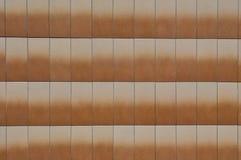 Tejas que hacen frente anaranjadas hechas de piedra en la pared del edificio foto de archivo