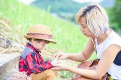 Tejido del uso de la mamá para limpiar la mano del niño en el parque Un sombrero del desgaste del niño foto de archivo