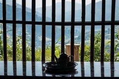 Tekanna framme av en träfönsterram Royaltyfria Bilder