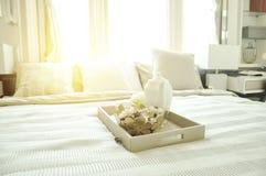 Tekanna i korgen på vit säng arkivfoton