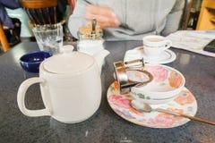 Tekanna med koppen och tefatet i teatime Royaltyfri Foto