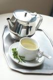 Tekanna och en kopp med grön örtte Arkivfoton