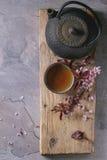 Tekanna och kopp te med blomningfilialen Royaltyfria Bilder