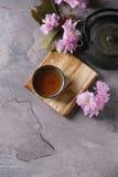 Tekanna och kopp te med blomningfilialen Royaltyfri Foto