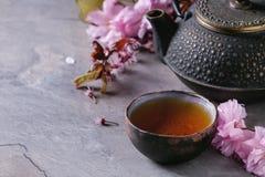 Tekanna och kopp te med blomningfilialen Arkivfoton