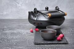 Tekanna och tekoppar för asiat svart traditionell med sunt växt- rosa te Royaltyfri Fotografi