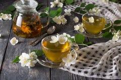 Tekannan med örtte, koppar med drinken, spridda jasminblommor på grå färger ytbehandlar Royaltyfri Fotografi