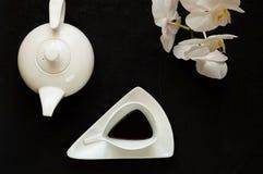 Tekannan och den vita keramiska koppen för tappning med kaffe på mörk bakgrund med orkidén blommar, kopieringsutrymme, closeup arkivfoto
