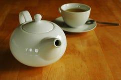 Tekannan och koppen av grönt te Arkivbilder