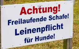 Teken ?Freilaufende Schafe Leinenpflicht f? ? r Hunde ?waarschuwt in het Duits over de gevaarsvergadering van hond en schapen op  stock afbeelding
