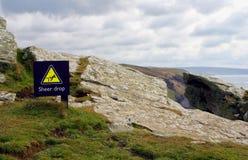 Teken bij de bovenkant die van een hoge kustklip, van het gevaar o waarschuwen stock afbeeldingen