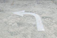 Teken van de close-up het witte geschilderde pijl in linkerkant op de vloerachtergrond van de cementstraat Royalty-vrije Stock Afbeelding