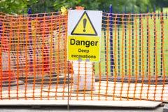 Teken van de gevaars het diepe uitgraving en oranje netto veiligheid stock foto's