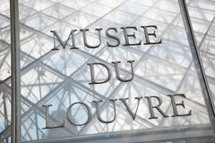 Teken van Louvremuseum op Piramideingang Stock Fotografie