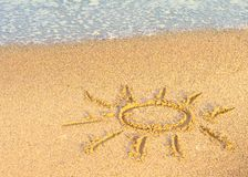 Tekening van de zon op zand met overzeese golf Stock Foto's