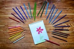 Tekening van een bloemnotitieboekje met kleurenpotloden op de houten lijst Royalty-vrije Stock Foto