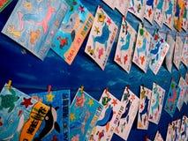 Tekeningen door jonge geitjes die op koord hangen Stock Afbeeldingen