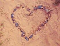 Tekeningshart van stenen op warm zand worden gelegd dat Gestemd, geconcentreerd zacht Royalty-vrije Stock Foto