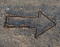 Tekeningspijl in het zand op het strand Stock Foto's