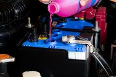 Tekniker är påfyllningvätska för batteribilen Arkivfoton