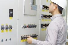Tekniker av techutrustningstyrning Arbetare i den vita hjälmen på kontrollbordet Övervakning av teknologiprocessen royaltyfri bild