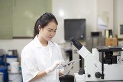 Tekniker eller kemi för kvinna som asiatisk gör det kemiska provet i laborat royaltyfria bilder