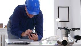 Tekniker i arkitekten Office med plan på skrivbordtexten genom att använda mobiltelefonnätverket arkivfilmer