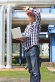 Tekniker i hardhat med bärbara datorn Fotografering för Bildbyråer