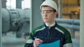 Tekniker i hardhat som går i fabrik och ner skriver på skrivplattan arkivfilmer