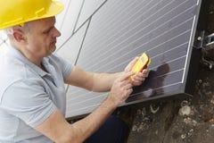 Tekniker Installing Solar Panels på taket av huset Royaltyfri Bild