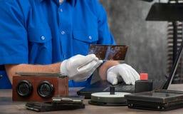 Tekniker med vita handskar som digitaliserar gammalt fotografi p? exponeringsglasplattan arkivfoto