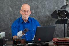 Tekniker med vita handskar som digitaliserar gammalt fotografi p? exponeringsglasplattan arkivfoton