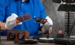 Tekniker med vita handskar som digitaliserar gammalt fotografi p? exponeringsglasplattan royaltyfri bild