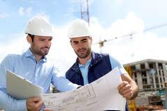 Tekniker och arbetare som kontrollerar plan på konstruktionsplats