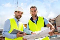 Tekniker och arbetare som kontrollerar plan på konstruktionsplats royaltyfri fotografi