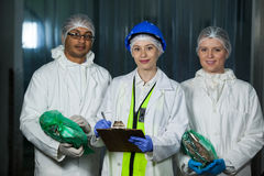 Tekniker och slaktare som rymmer den packade kött och skrivplattan arkivbild