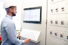 Tekniker på fjärrkontrollelkraftstation arkivfoto