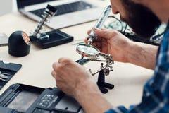 Tekniker som ändå löder förstoringsapparaten för microcircuit Royaltyfri Fotografi