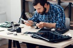 Tekniker som ändå löder förstoringsapparaten för microcircuit Arkivfoton