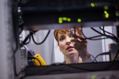 Tekniker som använder den digitala kabelanalysatorn på serveren Royaltyfri Bild
