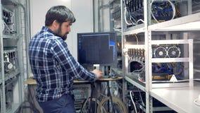 It-tekniker som arbetar i cryptocurrencyen som bryter fabriken Industriell bryta lantgård för bitcoin- och cryptocurrencypengar stock video