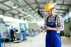 Tekniker som arbetar i fabrik och gör kvalitets- kontroll Arkivfoto