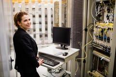 Tekniker som arbetar på datoren, medan analysera serveren fotografering för bildbyråer