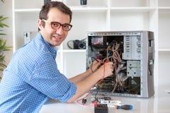Tekniker som arbetar på den brutna datoren i hans kontor Arkivbild