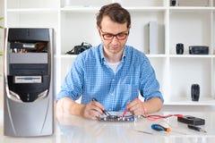 Tekniker som arbetar på den brutna datoren i hans kontor Royaltyfria Foton