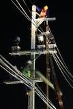 Tekniker som arbetar på elektriska Pole på natten Arkivbilder
