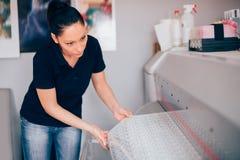 Tekniker som arbetar på plottar- och skäraremaskinen, i utskrift av cen arkivfoton