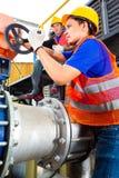 Tekniker som arbetar på ventilen i fabrik eller hjälpmedel Arkivbild